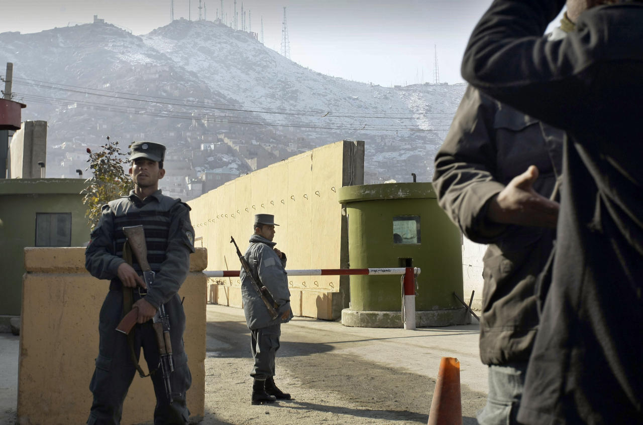 "FILE - In this Monday, Dec. 24, 2014 file photo, Afghan police officers stand guard outside of Kabul police headquarters, where a an American contractor was killed, in Kabul, Afghanistan. On Tuesday, Dec. 25, 2012, the Interior Ministry said a policewoman, identified as Sgt. Nargas, who shot and killed 49-year-old Joseph Griffin in Kabul on Monday, was a native Iranian who came to Afghanistan and displayed ""unstable behavior"" but had no known links to militants. It was the first such shooting by a woman in the spate of insider attacks. On Wednesday, Dec. 26, 2012, a suicide bombing at the gate of a major U.S. military base in eastern Afghanistan killed the attacker and three Afghans, Afghan police said. The Taliban claimed responsibility for the attack. NATO forces and foreign civilians have also been increasingly attacked by rogue Afghan military and police, eroding trust between the allies. (AP Photo/Musadeq Sadeq)"