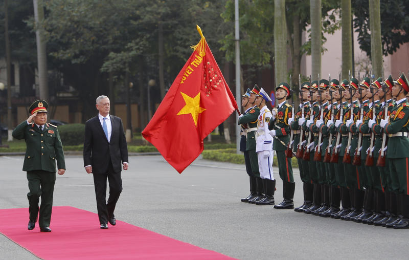 FILE - In this Jan. 25, 2018, file photo, U.S. Defense Secretary Jim Mattis and his Vietnamese counterpart Ngo Xuan Lich, left, review an honor guard in Hanoi, Vietnam. By making a rare second trip this year to Vietnam, Mattis is showing how intensively the Trump administration is trying to counter China's military assertiveness by cozying up to smaller nations in the region who share American wariness about Chinese intentions. The visit beginning Tuesday also shows how far U.S.-Vietnamese relations have advanced since the tumultuous years of the Vietnam War, whose legacy includes a continued search for the remains of U.S. war dead on Vietnamese soil. (AP Photo/Tran Van Minh, File)