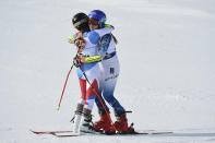 Gold medalist Switzerland's Lara Gut-Behrami, left, embraces silver medalist United States' Mikaela Shiffrin after a women's giant slalom, at the alpine ski World Championships, in Cortina d'Ampezzo, Italy, Thursday, Feb. 18, 2021. (AP Photo/Marco Tacca)