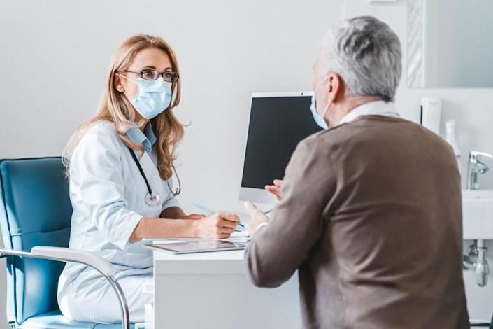 Woman doctor wear protection face mask talking with patient in clinic office