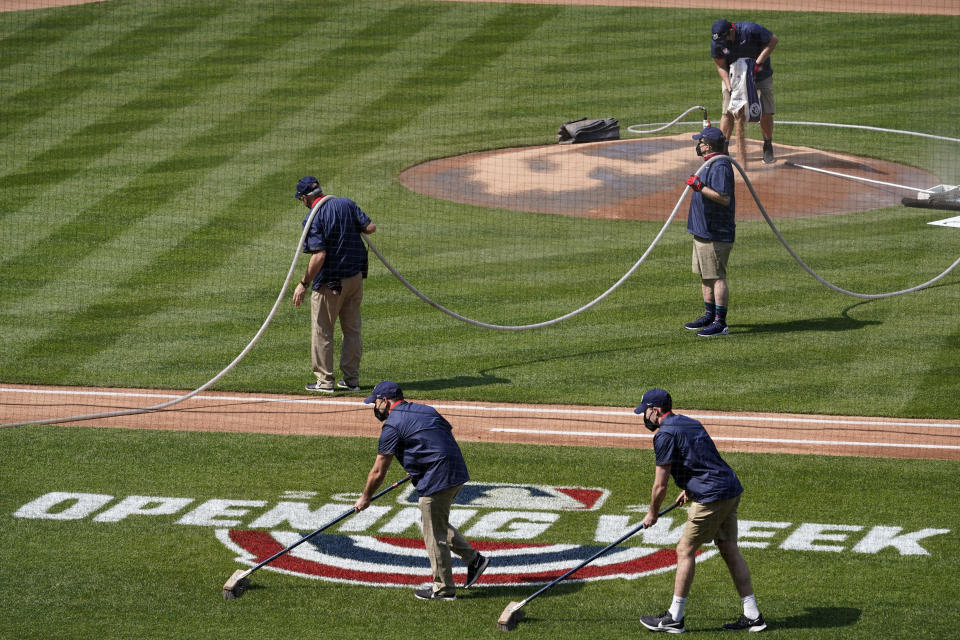 Groundskeepers prepare the field before a home opener baseball game between the Atlanta Braves and the Washington Nationals at Nationals Park, Tuesday, April 6, 2021, in Washington. (AP Photo/Alex Brandon)