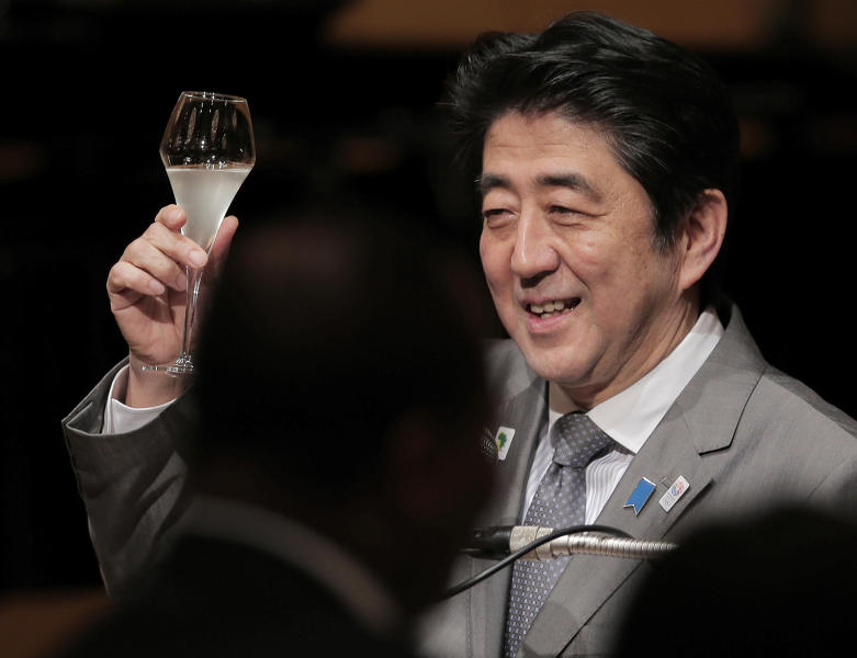 Japanese Prime Minister Shinzo Abe raises a glass for a toast during the official dinner with African leaders hosted by Abe at the Tokyo International Conference on African Development (TICAD) in Yokohama, near Tokyo, Sunday, June 2, 2013. Japan announced Sunday a plan to provide 100 billion yen ($1 billion) in aid over the next five years to northern Africa for economic development and humanitarian efforts, including help with security and counter-terrorism measures. (AP Photo/Itsuo Inouye)