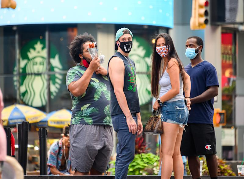 NEW YORK, NEW YORK - AUGUST 05: People wear protective face masks outside Starbucks in Times Square as the city continues Phase 4 of re-opening following restrictions imposed to slow the spread of coronavirus on August 5, 2020 in New York City. The fourth phase allows outdoor arts and entertainment, sporting events without fans and media production. (Photo by Noam Galai/Getty Images)