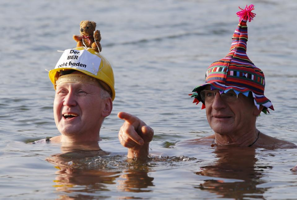 """Members of the Berliner Seehunde (Berlin Seals) ice swimmers club take a dip in Lake Orankesee during their traditional New Year swimming event in Berlin, January 1, 2015. The words on the helmet (L) reads """"The Berlin Brandenburg international airport BER is totally unsuccessful."""" REUTERS/Fabrizio Bensch (GERMANY - Tags: SOCIETY SPORT SWIMMING)"""