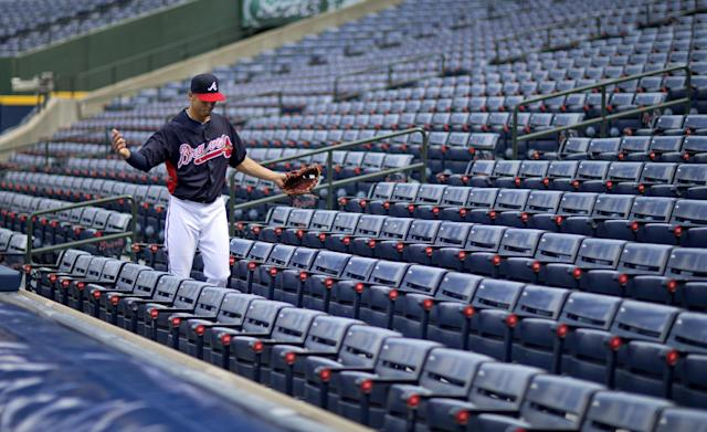 Atlanta Braves' Andrelton Simmons looks for a ball that went into the stands during a baseball practice on Wednesday, Oct. 2, 2013, in Atlanta. The Los Angeles Dodgers play the Braves in Game 1 of the National League Division Series in Atlanta, Thursday. (AP Photo/David Goldman)