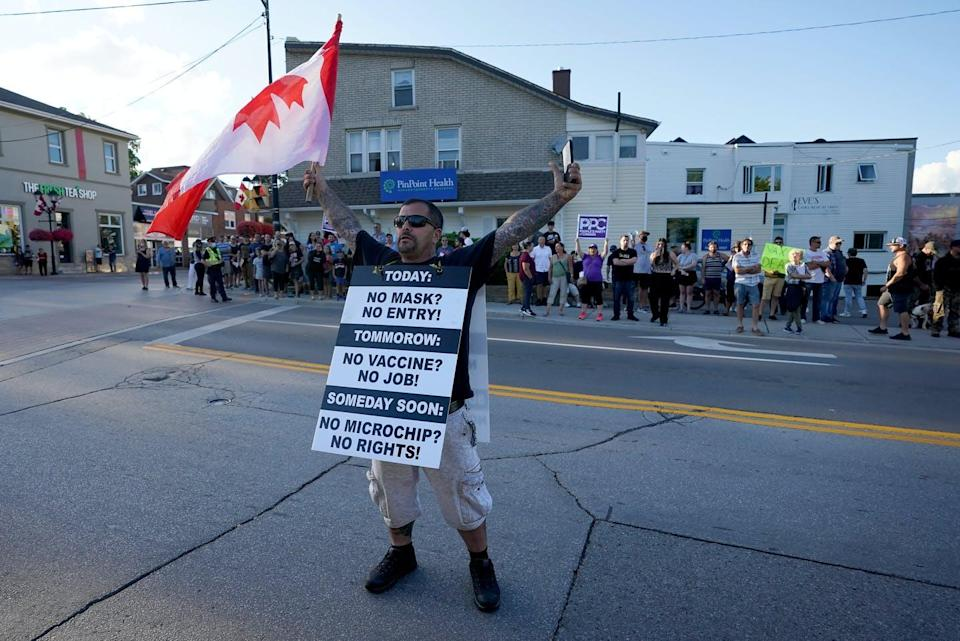 """<span class=""""caption"""">An anti-vaccination protester holds an upside down Canadian flag during a demonstration outside the venue of a Liberal Party election campaign event, in Newmarket, Ont.</span> <span class=""""attribution""""><span class=""""source"""">THE CANADIAN PRESS/Nathan Denette</span></span>"""