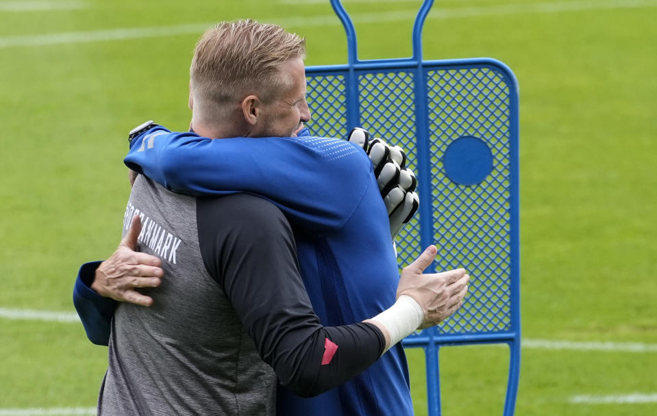 Denmark's goalkeeper Kasper Schmeichel is embraced at the training ground during a training session of Denmark's national team in Helsingor, Denmark, Monday, June 14, 2021. It is the first training of the Danish team since the Euro championship soccer match against Finland when Christian Eriksen collapsed last Saturday. (AP Photo/Martin Meissner)