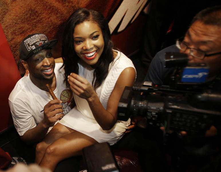 The Miami Heat's Dwyane Wade celebrated with his girlfriend Gabrielle Union after Game 7 of the NBA basketball championship against the San Antonio Spurs, Friday, June 21, 2013, in Miami. The Miami Heat defeated the San Antonio Spurs 95-88 to win their second straight NBA championship. (AP Photo/Wilfredo Lee)