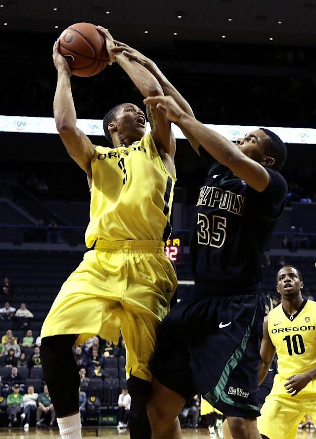 Oregon guard Joseph Young, left, is fouled while shooting by Cal Poly guard Kyle Odister during the first half of an NCAA college basketball game in Eugene, Ore., Sunday, Dec. 1, 2013. (AP Photo/Don Ryan)