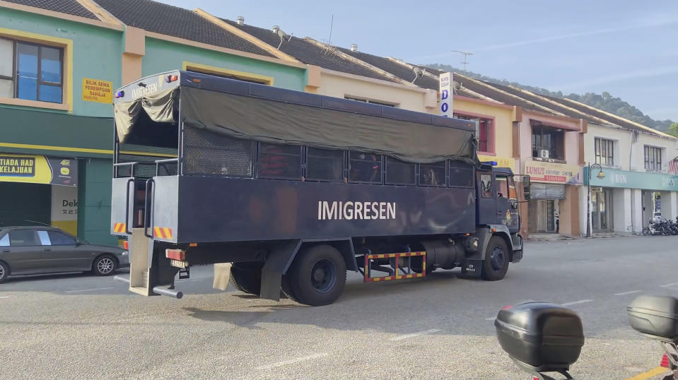 In this image taken from a video, an immigration truck with unidentified people onboard is driven on a road that leads to Lumut Naval Base Tuesday, Feb. 23, 2021 in Lumut, Malaysia. A Malaysian court Tuesday ordered a halt to the planned deportation of 1,200 Myanmar migrants to hear an appeal by two human rights groups, which say the migrants included refugees, asylum seekers and minors. (AP Photo)