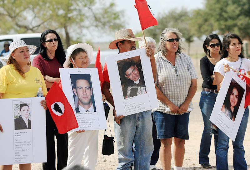 Members of LUPE hold photos of people who have been killed by law enforcement, according to the Southern Border Communities Coalition, during a news conference and vigil Thursday Nov. 1, 2012, on the corner of Farm-to-Market Road 2221 and Mile 7 near La Joya, Texas. The Texas trooper who fired on a fleeing pickup truck from a helicopter near the U.S.-Mexico border, killing two illegal immigrants hiding in the bed, has returned to work but in a different role, the state Department of Public Safety said Thursday. The announcement came less than an hour after the American Civil Liberties Union and local civil rights organizations gathered near the site of the Oct. 25 shooting to demand an investigation by an independent body outside the agency. (AP Photo/The Monitor, Gabe Hernandez)
