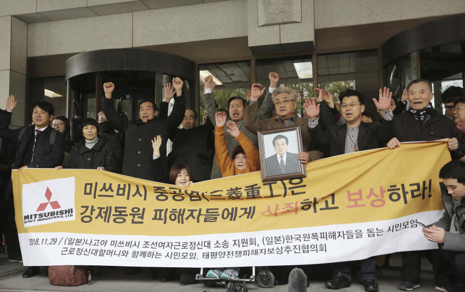 "FILE - In this Nov. 29, 2018, file photo, South Korean victims of Japan's forced labor and their family members raise their hands in celebration after the Supreme Court's ruling ordering Japan's Mitsubishi Heavy Industries to compensate them in Seoul, South Korea. The modern legacy of a dark chapter in Japan's history, when hundreds of thousands of people were brought from the Korean Peninsula and other Asian nations to work in logging, in mines, on farms and in factories as forced labor, lives on in the companies that came to dominate the Japanese economy after World War II. Many of those companies are still facing demands for compensation that they say were settled by treaty decades ago. The signs read: ""Mitsubishi Heavy Industries apologizes and compensates to victims."" (AP Photo/Ahn Young-joon, File)"
