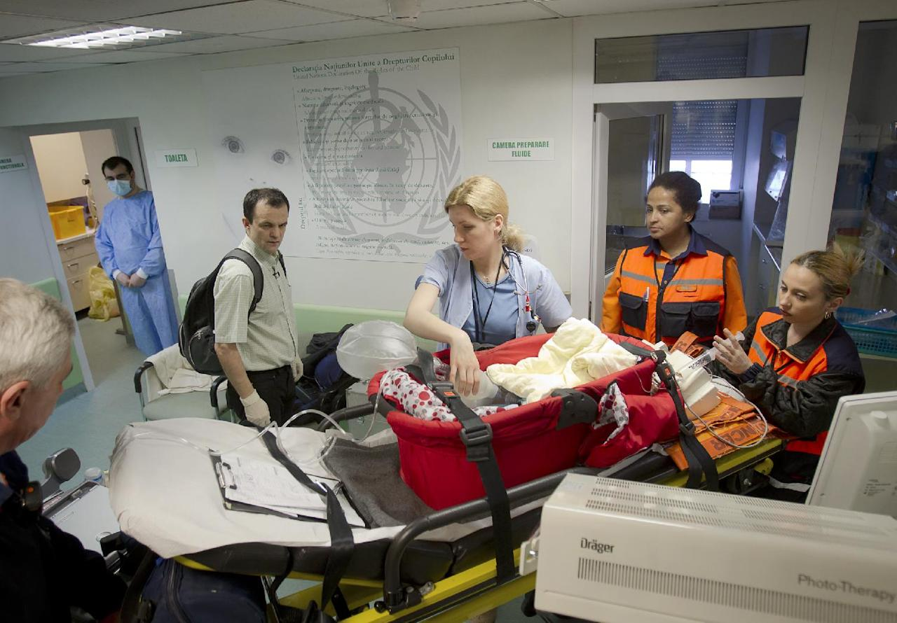 Doctor Catalin Cirstoveanu, left, with backpack, watches as a newborn baby is transported to an ambulance on his way to Italy for heart surgery from the intensive care unit of the Marie Curie children's hospital, on March 22, 2012, in Bucharest, Romania. Cirstoveanu is fighting an exhausting and largely solitary battle against a culture of corruption and indifference toward patient welfare that's deeply embedded in Romania.Last year, some 2,800 Romanian doctors _ discouraged by the antiquated and corrupt health system and low wages _left to work in Western Europe, according to the Council of Medics.(AP Photo/Vadim Ghirda)