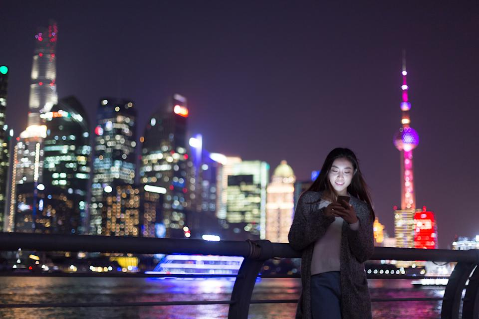 Young Chinese woman using phone in Shanghai