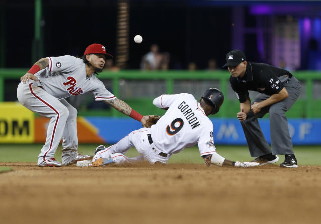 Philadelphia Phillies shortstop Freddy Galvis is unable to hang on to the throw as Miami Marlins' Dee Gordon (9) slides into second base before advancing to third as second base umpire Roberto Ortiz looks on during the fifth inning of a baseball game, Thursday, Aug. 31, 2017, in Miami. (AP Photo/Wilfredo Lee)