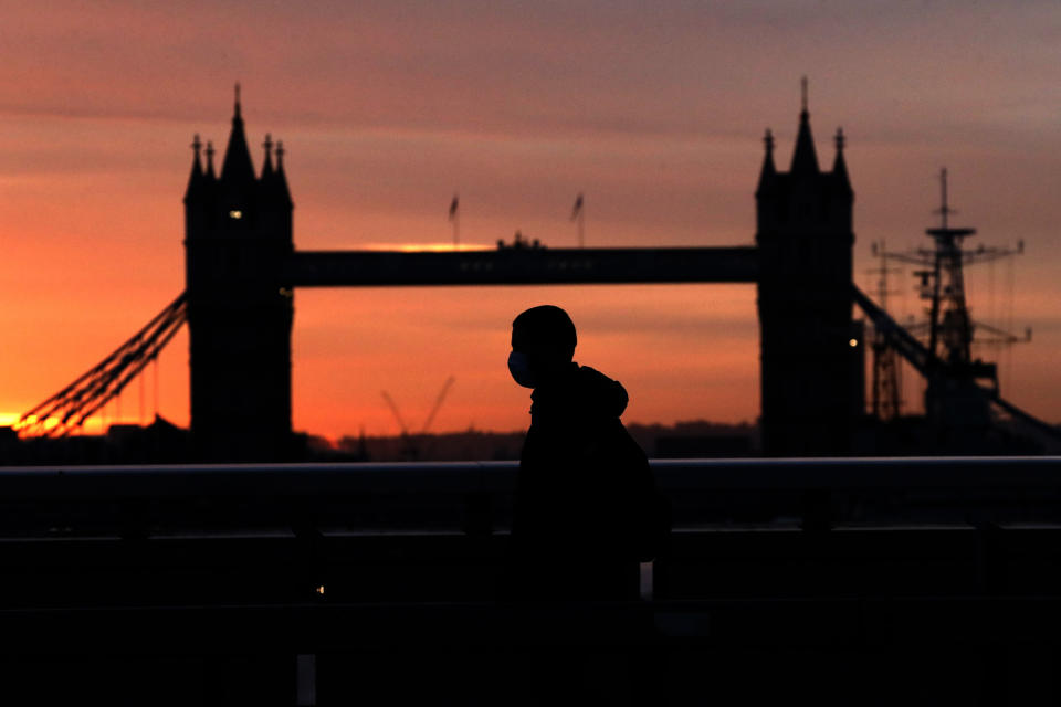 "A person wearing a face mask to try to stop the spread of coronavirus walks across London Bridge, with Tower Bridge in the background, at sunrise in London, Monday, Oct. 12, 2020. In response to the coronavirus' resurgence, British Prime Minister Boris Johnson is expected to announce in Parliament on Monday a three-tier local lockdown system, formally known as ""Local COVID Alert Levels,"" for England, his office said. (AP Photo/Matt Dunham)"