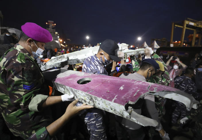Soldiers and rescue personnel carry debris found in the waters off Java Island around where a Sriwijaya Air passenger jet crashed on Saturday, at Tanjung Priok Port in Jakarta, Indonesia, Sunday, Jan. 10, 2021. Indonesian rescuers pulled out body parts, pieces of clothing and scraps of metal from the Java Sea early Sunday morning, a day after a Boeing 737-500 with dozens of people onboard crashed shortly after takeoff from Jakarta, officials said. (AP Photo/Dita Alangkara)
