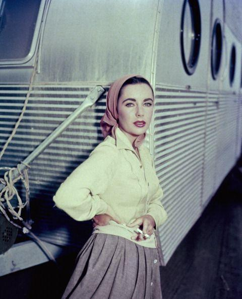 <p>Elizabeth is seen leaning against her dressing room trailer and smoking a cigarette during a break from filming on the set of <em>Giant</em>. </p>