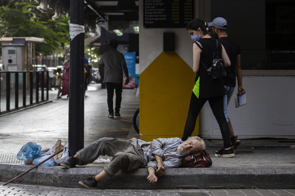 FILE - In this July 17, 2020 file photo, a woman looks at a homeless Lebanese man sleeping on the ground in Hamra street, in Beirut, Lebanon. Minister of Tourism and Social Affairs Ramzi Moucharafieh said Thursday, Sept 9, 2021, during a news conference, in Beirut that the government will start paying cash assistance next month to hundreds of thousands of poor families - in U.S. dollars - as the small nation sinks deeper into its economic crisis. (AP Photo/Hassan Ammar, File)
