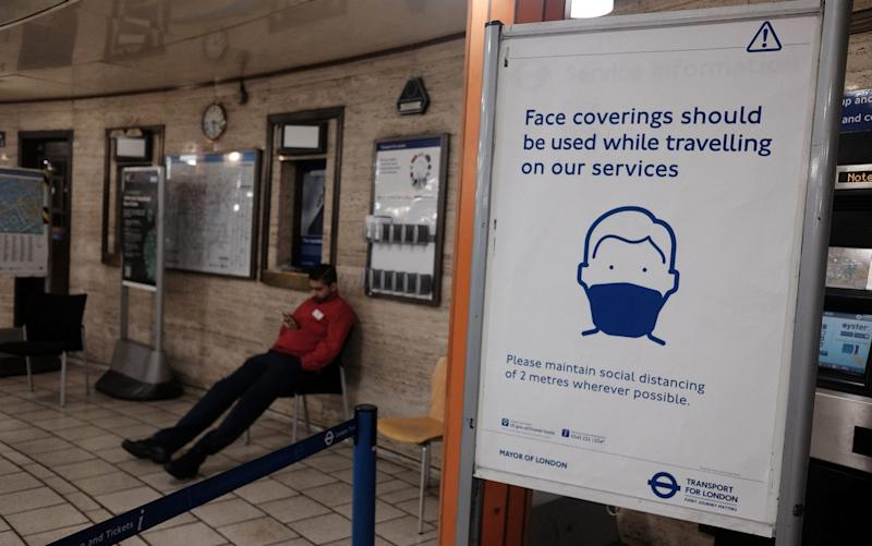 A sign advising the use of face coverings for commuters at Piccadilly Circus Underground station in London - PA