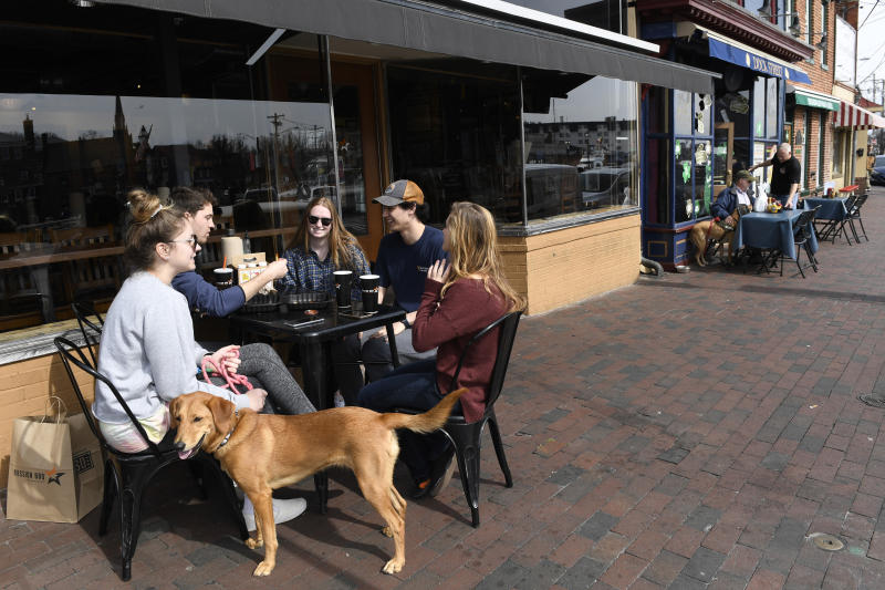 Friends, from left, Erin Carroll of Severna Park, Md., Clay Colehouse of Crownsville, Md., Jessica Goblin of Severna Park, Md., Travis Victorio of Millersville, Md., Mary Fitzell of Millersville, Md., and dog Marty, enjoy lunch during a visit to Annapolis, Monday, March 16, 2020. Maryland Gov. Larry Hogan ordered the closure of bars, restaurants, gyms and movie theaters across the state in response to coronavirus beginning at 5 p.m. Monday. Drive-thru, carryout and delivery service will still be allowed. The friends gathered for lunch because they are home from college. (AP Photo/Susan Walsh)