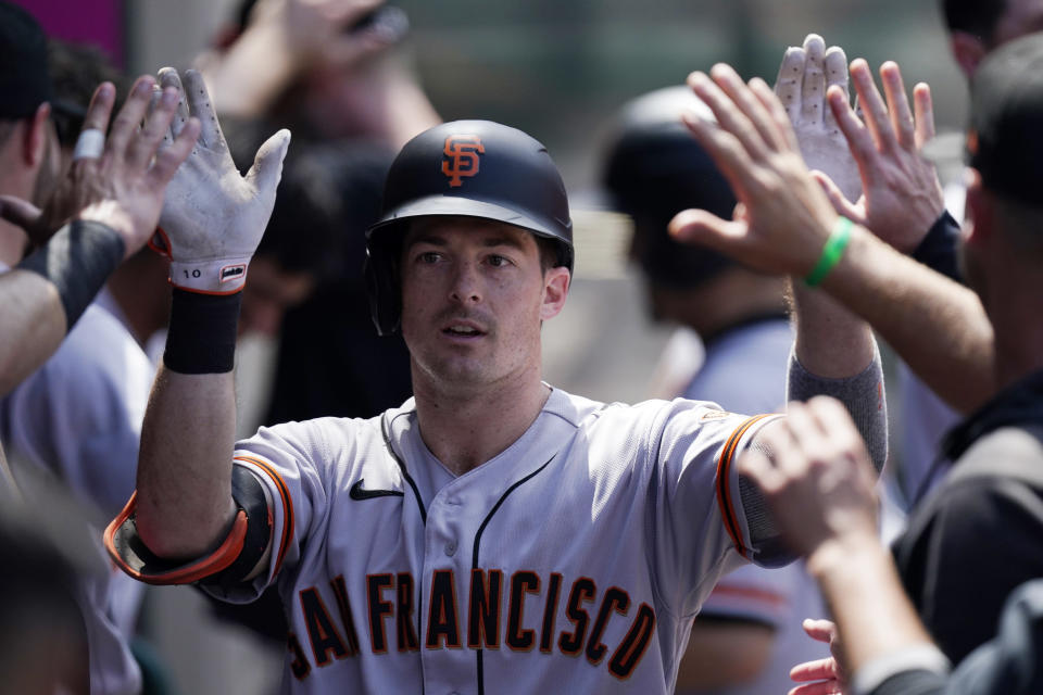 San Francisco Giants' Mike Yastrzemski is congratulated by teammates in the dugout after hitting a solo home run during the fifth inning of a baseball game against the Los Angeles Angels Wednesday, June 23, 2021, in Anaheim, Calif. (AP Photo/Mark J. Terrill)