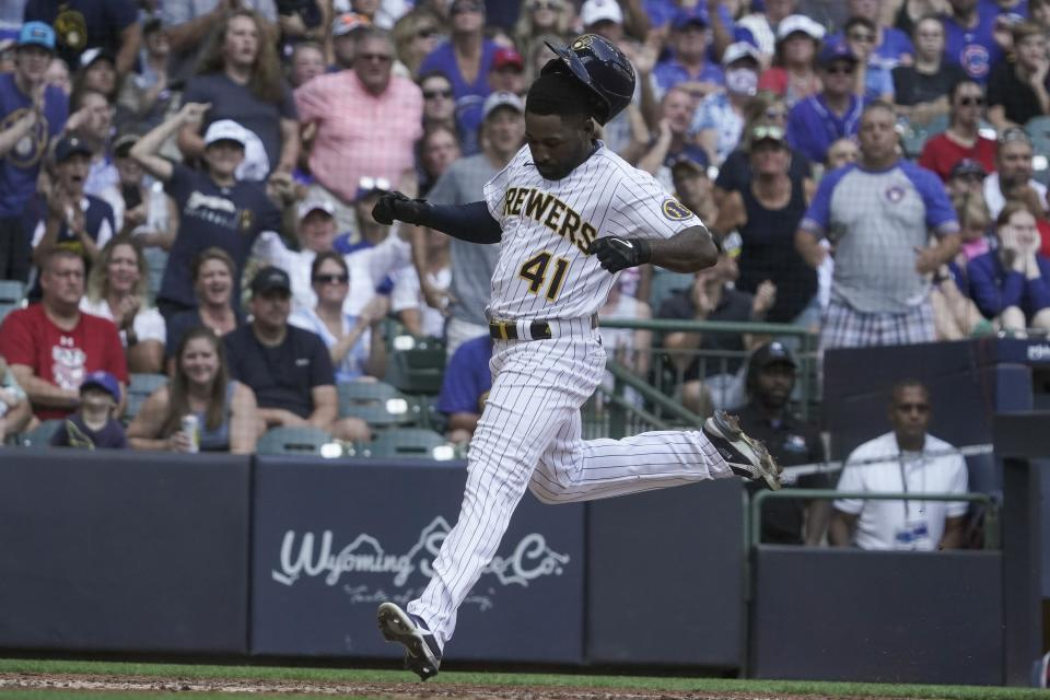 Milwaukee Brewers' Jackie Bradley Jr. loses his helmet as he scores from first on a double by Kolten Wong during the fifth inning of a baseball game against the Chicago Cubs Sunday, Sept. 19, 2021, in Milwaukee. (AP Photo/Morry Gash)