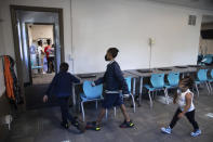 In this Friday, Oct. 1, 2021 photo, from left, Zihare Wellons, 7, Shahif Wellons, 12, and Janiyah Acie, 3 walk through new Rec2Tech space at Jefferson Recreation Center, which will provide access to technology and innovative programming for community members including STEM, computer science and coding education, combined with the arts in Pittsburgh. The city plans to use some of the money from the American Rescue Plan, passed by Congress last spring, to continue expanding these programs. Initial programming will be for young people, with plans to grow the programming into the broader community. (AP Photo/Rebecca Droke)