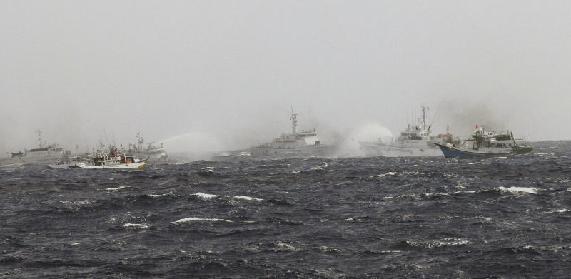 In this photo released by Taiwan's Central News Agency, Japan Coast Guard patrol boats spray their water cannons towards a Taiwan Coast Guard patrol boat and Taiwanese fishing boats near the disputed islands called Senkaku in Japan and Diaoyu in China, in the East China Sea, Tuesday, Sept. 25, 2012. On Tuesday morning, about 50 Taiwanese fishing boats accompanied by 10 Taiwanese surveillance ships came within almost 20 kilometers (about 12 miles) of the disputed islands - within what Japan considers to be its territorial waters. (AP Photo/Central News Agency) TAIWAN OUT