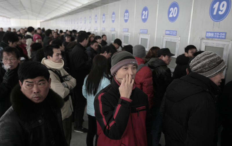 In this Thursday, Jan. 27, 2011 photo, passengers line up to buy train tickets sold in advance at a temporary advance ticket sale windows for the Chinese new year at the Shanghai Railway Station in Shanghai, China. China's 91,000 kilometers (56,400 miles) of railways are the world's longest and, in some cases, the fastest. The country's drive to develop high-speed rail technology rivals its space program in terms of national pride and importance. But the annual scrum for tickets home for the year's major festival _ the world's biggest annual migration involving 230 million people _ highlights the wide gap between showcase Chinese infrastructure and the often abysmal services available to the public. (AP Photo/Eugene Hoshiko)