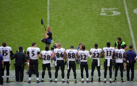 Sep 24, 2017; London, United Kingdom; Baltimore Ravens quarterback Joe Flacco (5) and coach John Harbaugh interlock arms with players during the playing of the United States national anthem before the NFL International Series game against the Baltimore Ravens at Wembley Stadium. Mandatory Credit: Kirby Lee-USA TODAY Sports