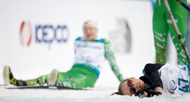 Cross-Country Skiing - Pyeongchang 2018 Winter Paralympics - Women's 15km Free - Visually Impaired - Alpensia Biathlon Centre - Pyeongchang, South Korea - March 12, 2018 - Yadviha Skorabahataya of Belarus and Mikhalina Lysova, paralympic athlete from Russia, react after crossing the finish line. REUTERS/Carl Recine