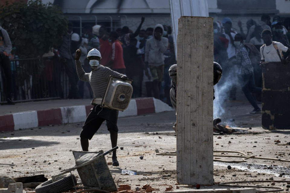 Demonstrators throw rocks at riot policemen during protests at the Cheikh Anta Diop University campus in Dakar, Senegal, against the arrest of opposition leader and former presidential candidate Ousmane Sonko, Thursday, March 4, 2021. (AP Photo/Leo Correa)