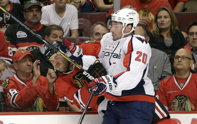 Washington Capitals right wing Troy Brouwer (20) checks Chicago Blackhawks defenseman Brent Seabrook into the boards during the first period of an NHL hockey game Tuesday, Oct. 1, 2013, in Chicago. (AP Photo/Nam Y. Huh)