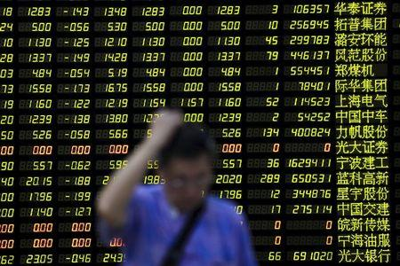 An investor stands in front of electronic board showing stock information at brokerage house in Shanghai