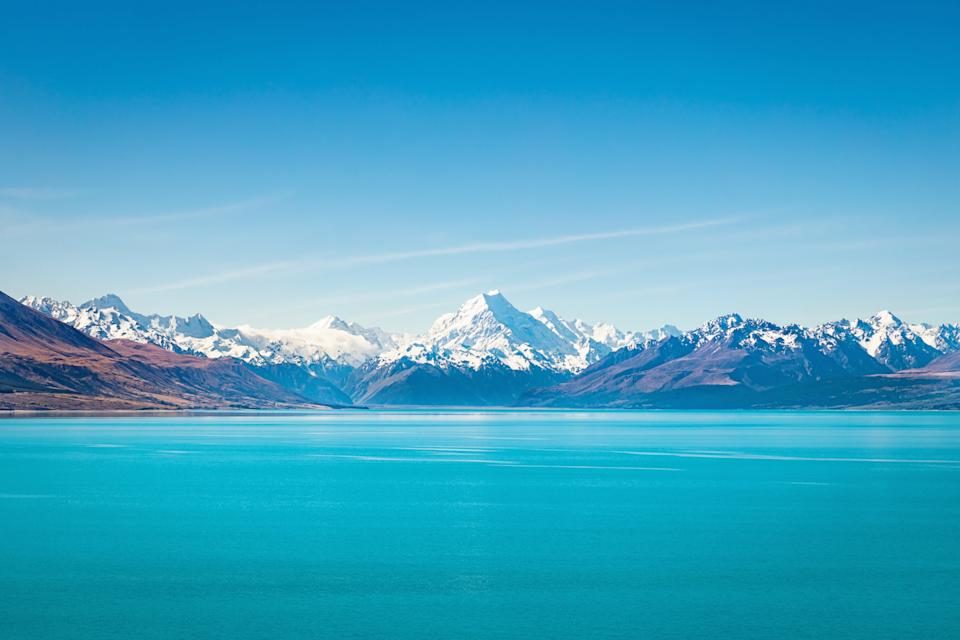 Beautiful turquoise Lake Tekapo under blue cloudless summer sky. The famous snow covered Aoraki Mount Cook in the background at the horizon. Lake Tekapo, Aoraki Mount Cook National Park, Caterbury, New Zealand.