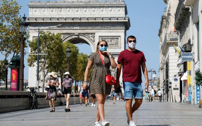 People wearing protective masks walk on the Champs-Elysees near the Arc de Triomphe - CHARLES PLATIAU/Reuters