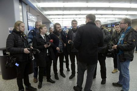 A man (facing back) who did not want to reveal his name talks to the representatives of the media waiting for the arrival of Choe Kang-il, a senior diplomat from North Korea, at the Helsinki International airport in Vantaa, Finland, March 18, 2018. LEHTIKUVA/Vesa Moilanen/via REUTERS