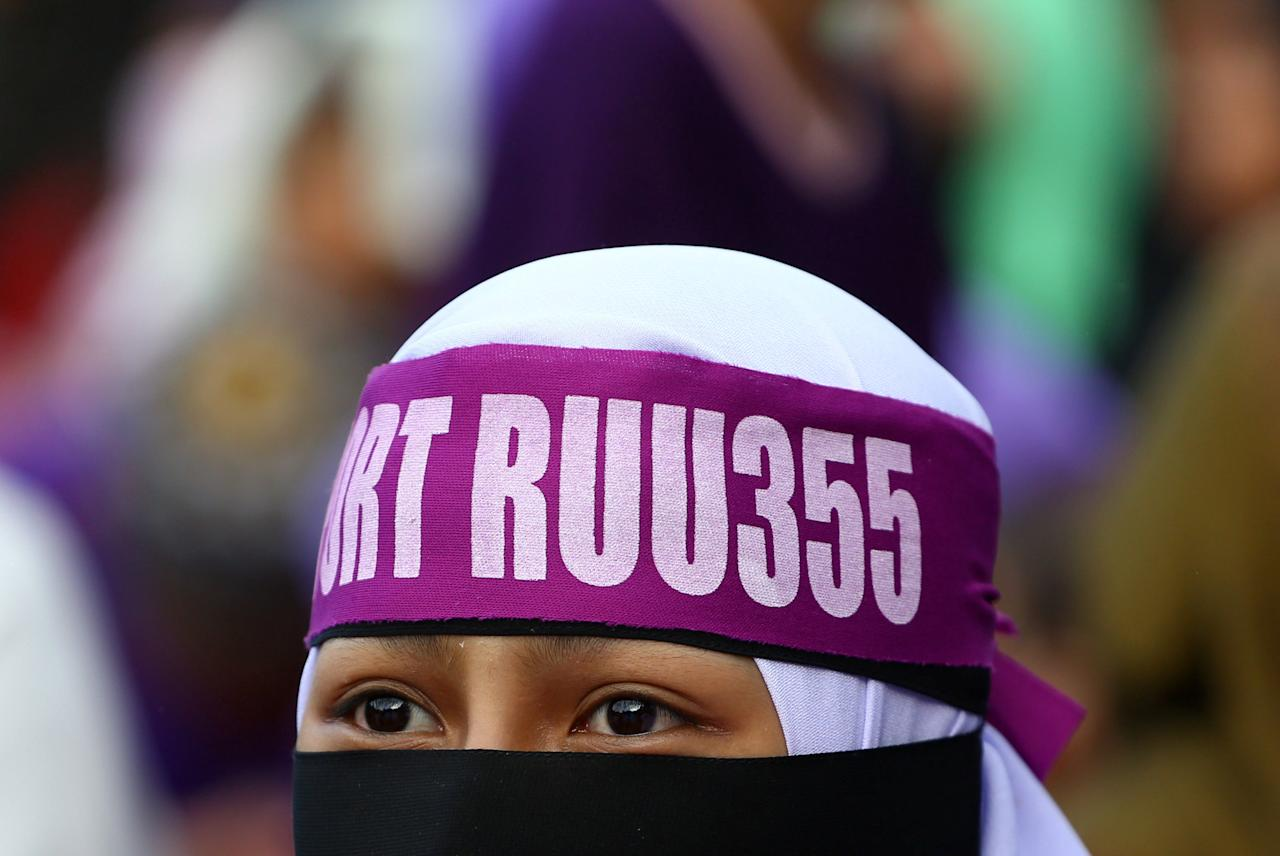 A supporter attends a rally to support the adoption of a strict Islamic penal code at Padang Merbok in Kuala Lumpur, Malaysia, February 18, 2017. REUTERS/Athit Perawongmetha     TPX IMAGES OF THE DAY