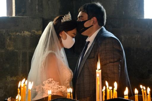 Conspiracy claims and alleged failure to take the virus threat seriously have seen cases incrase in Armenia -- here a bride and a bridegroom did don masks for their wedding at Saghmosavan near the capital