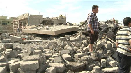 Civilians gather at the site of a bomb attack in the village of Mwafaqiya