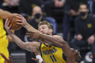 Indiana Pacers forward Domantas Sabonis (11) pulls down an offensive rebound over Charlotte Hornets center Bismack Biyombo in the first half of an NBA basketball game in Charlotte, N.C., Wednesday, Jan. 27, 2021. (AP Photo/Nell Redmond)