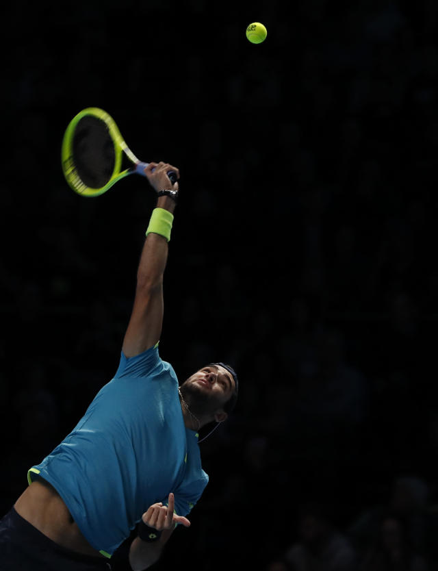Italy's Matteo Berrettini serves to Serbia's Novak Djokovic during their ATP World Tour Finals singles tennis match at the O2 Arena in London, Sunday, Nov. 10, 2019. (AP Photo/Alastair Grant)