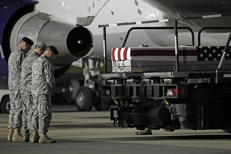 Chaplain Col. Dennis Goodwin, left, directs a prayer over the transfer case containing the remains of Army Capt. Bruce K. Clark of Spencerport, N.Y., upon arrival at Dover Air Force Base, Del. on Thursday May 3, 2012. The Department of Defense announced the death of Clark who was supporting Operation Enduring Freedom in Afghanistan. (AP Photo/Jose Luis Magana)