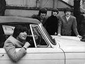 <p>John Lennon of the British pop group the Beatles sits in his car after passing his driving test, February 16, 1965. Bandmates George Harrison, Ringo Starr, and Paul McCartney show their support. </p>
