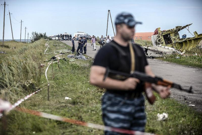 Armed pro-Russian separatists stand guard in front of the crash site of Malaysia Airlines Flight MH17, near the village of Grabove, in the region of Donetsk on July 20, 2014