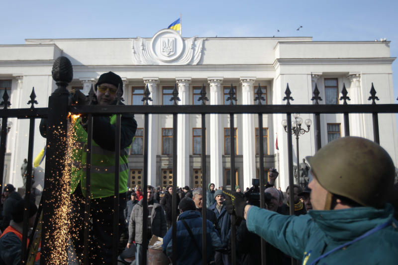 Anti-Yanukovych protesters remove a fence that surrounds Ukraine's parliament in Kiev, Wednesday, Feb. 26, 2014. Ukraine has been consumed by a three-month-long political crisis. President Viktor Yanukovych and protest leaders signed an agreement last week to end the conflict that left more than 80 people dead in just a few days in Kiev. Shortly after, Yanukovych fled the capital for his powerbase in eastern Ukraine but his exact whereabouts are unknown. (AP Photo/Sergei Chuzavkov)