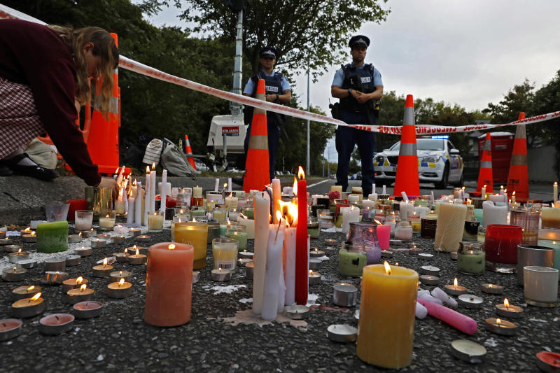 FILE - In this March 18, 2019, file photo, a student lights candle during a vigil to commemorate victims of March 15 shooting, outside the Al Noor mosque in Christchurch, New Zealand. New Zealanders are debating the limits of free speech after their chief censor banned a 74-page manifesto written by a man accused of massacring 50 people at two mosques. (AP Photo/Vincent Yu, File)