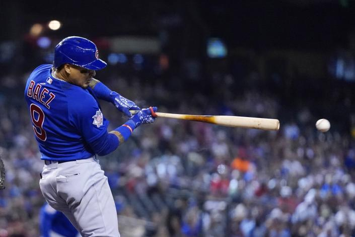 Chicago Cubs' Javier Baez connects for a run-scoring single against the Arizona Diamondbacks during the sixth inning of a baseball game, Sunday, July 18, 2021, in Phoenix. (AP Photo/Ross D. Franklin)