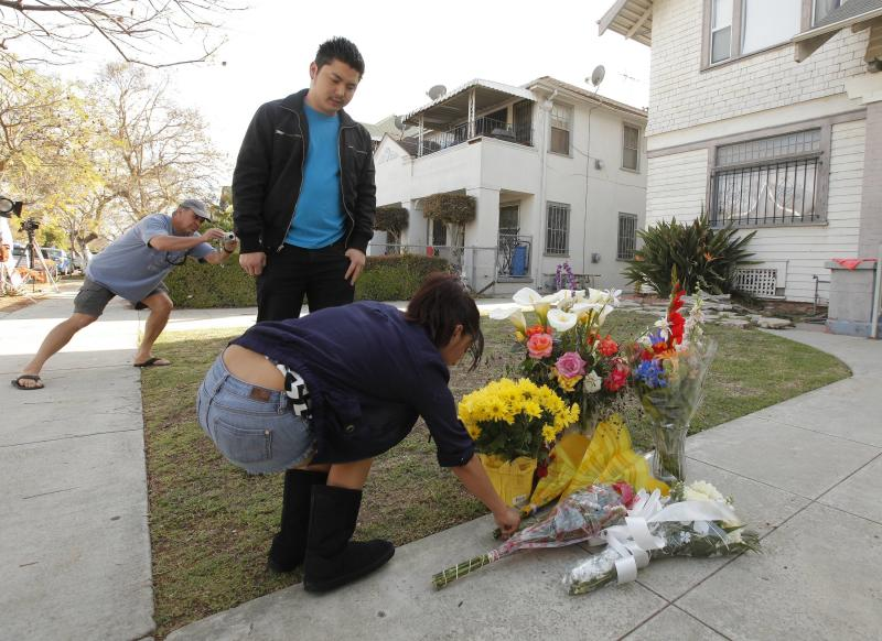 Neighbors Araceli Van Dine, right, and Derek Van Dine, middle, bring flowers to the site of the slayings of two USC graduate students early Wednesday, April 11, 2012 in Los Angeles. Neighbor Ron Veto, at left, takes a photo. Police said a gunman opened fire on a BMW near the University of Southern California campus on Wednesday, killing two international students from China in what may have been a bungled carjacking attempt. (AP Photo/Damian Dovarganes)